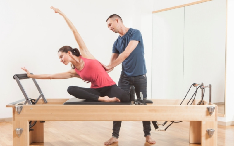 young woman exercising on pilates machine